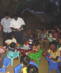 Children enjoying the chairs and desks donated by Emower a Villge