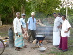 Villagers make the customary milk rice to celebrate the successful drilling phase; the tube well is on the left